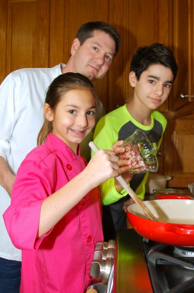 """Claire, who Brett calls """"my little sous chef,"""" stirs the pan while brother Andrew adds ingredients and father Brett supervises."""