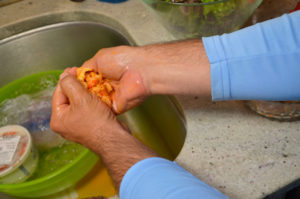 Todd always squeezes any excess moisture from bagged, frozen crawfish tail meat with his hands before using it.
