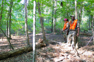 William and Jenni Washington follow a deer trail, investigating a good place to locate a stand.