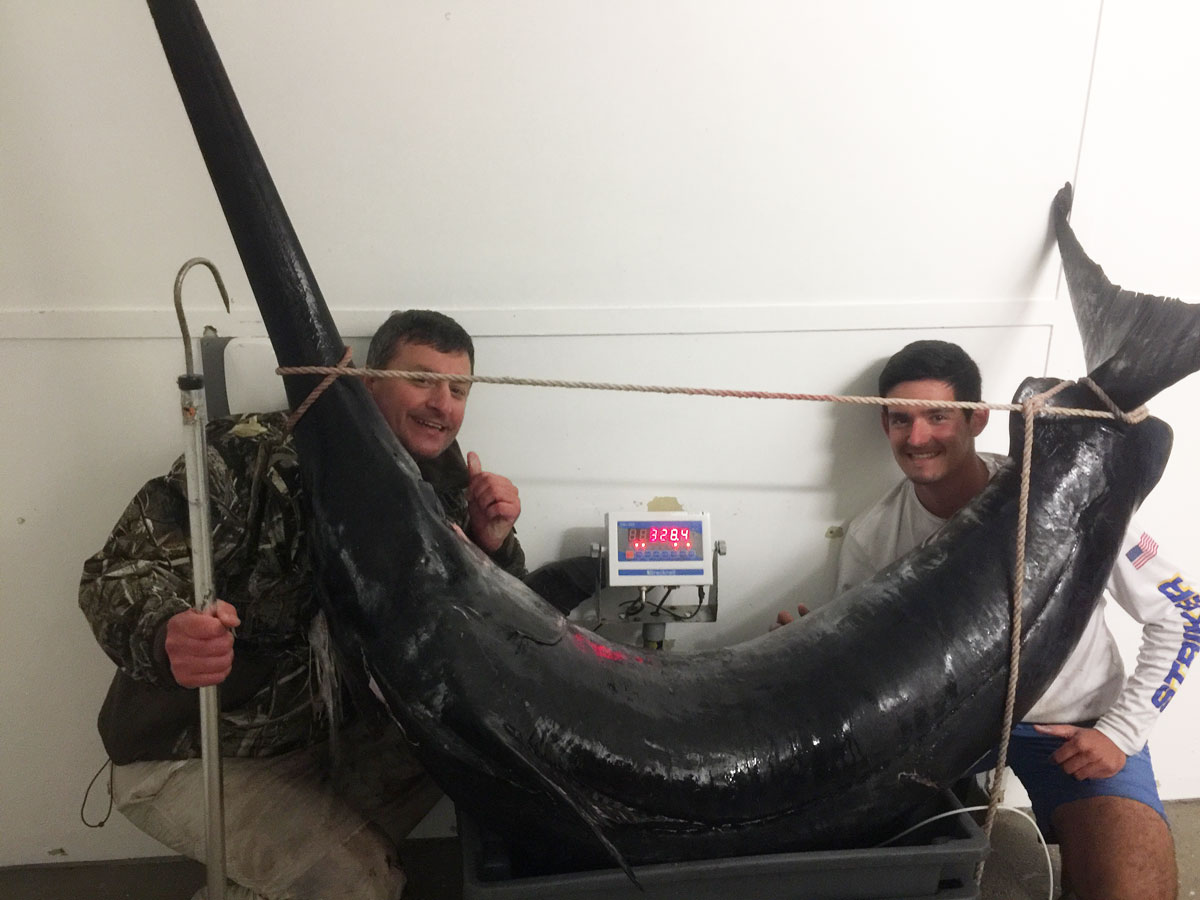 At Venice Marina, Chris Negulescu, left, and his nephew Alex Negulescu, pose with the 328.4-pound swordfish they caught Saturday afternoon in 1,200 feet of water out of Venice. Because the giant sword was harvested with an electric reel, it does not qualify for the state record books
