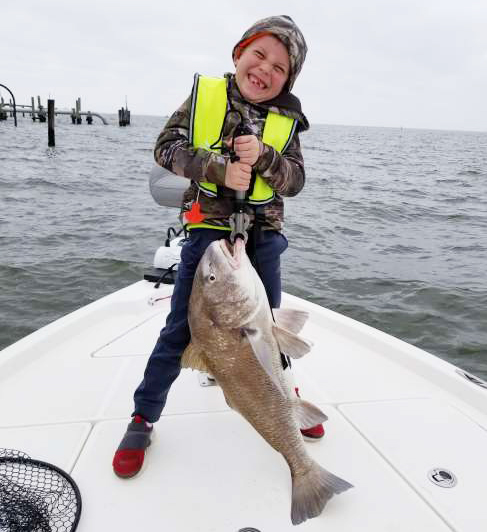 Hudson Brister's arms hurt after reeling in this 15-pound black drum.