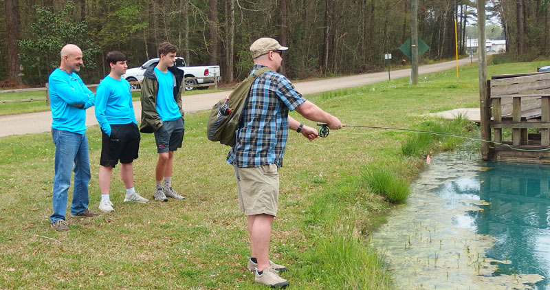 From left, Kevin Andry and St. Micheal Fly Fishing Club members Brayden Burleigh and Tanner Pike watch on as Red Stick Fly Fishers Education Director Sydney Dobson gives a casting lesson.