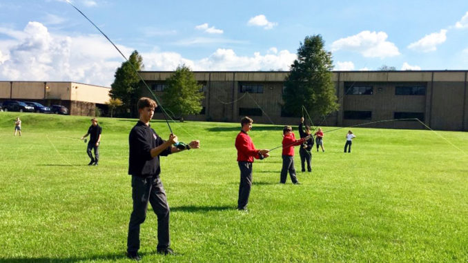 Some members of the St. Michael Fly Fishing Club practice casting on school grounds at one of their after-school meetings. Only half the members can practice at one time due to shortage of equipment.