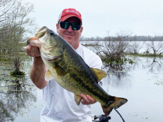 Brett Trouille, of Maurice, shows off the 10.03-pound largemouth he caught March 30 in the 12-15 area. The big bass, which was bedded down, bit a white Texas-rigged Zoom Craw.