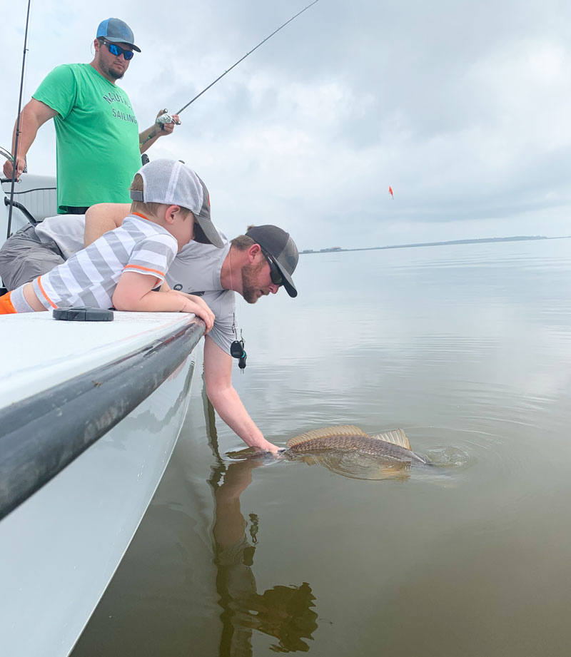 Nick Poe releases a big redfish.