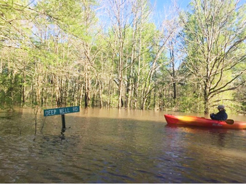 A kayaker makes his way down the flooded Deep Well Road through Ouachita River floodwaters at Rocky Branch.