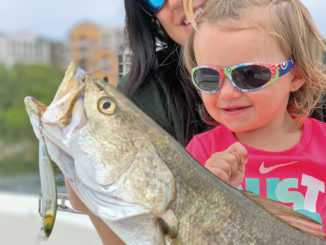 Charleigh Champagne, the 2 1/2-year-old daughter of Matrix Shad owner Chas Champagne, admires a huge speckled trout that fell for a Matrix Rip Shad.