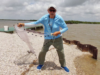 Clay Peltier prepares to throw a cast net at the Big Dam along Bird Island Bayou in Marsh Island.