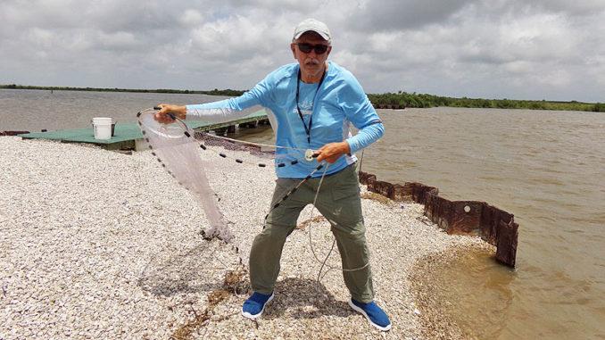 Clay Peltier prepares to throw a cast net at the Big Dam along Bird Island Bayou in Marsh Island.
