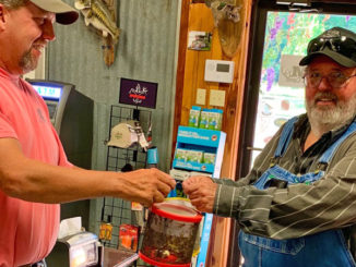 Kenny Kavanaugh serves up a bucket of crickets to a customer at K&M in Farmerville.