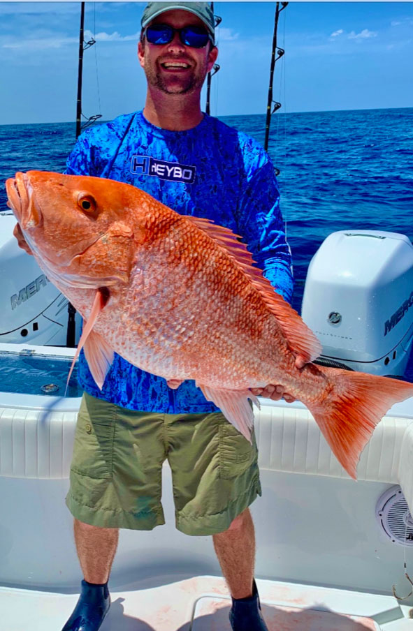 Hunter Adams, future son-in-law of Larry Doiron Jr., hefts a huge red snapper caught on Doiron's Reel Deal on a trip out of Grand Isle.