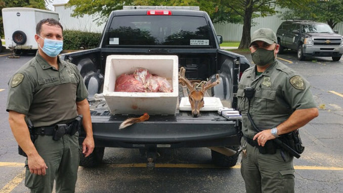 Agents with seized deer that was taken at night and out of season.