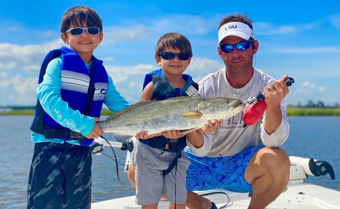 John Solari's sons, Tripp and Phillip, show off their dad's STAR champion trout.