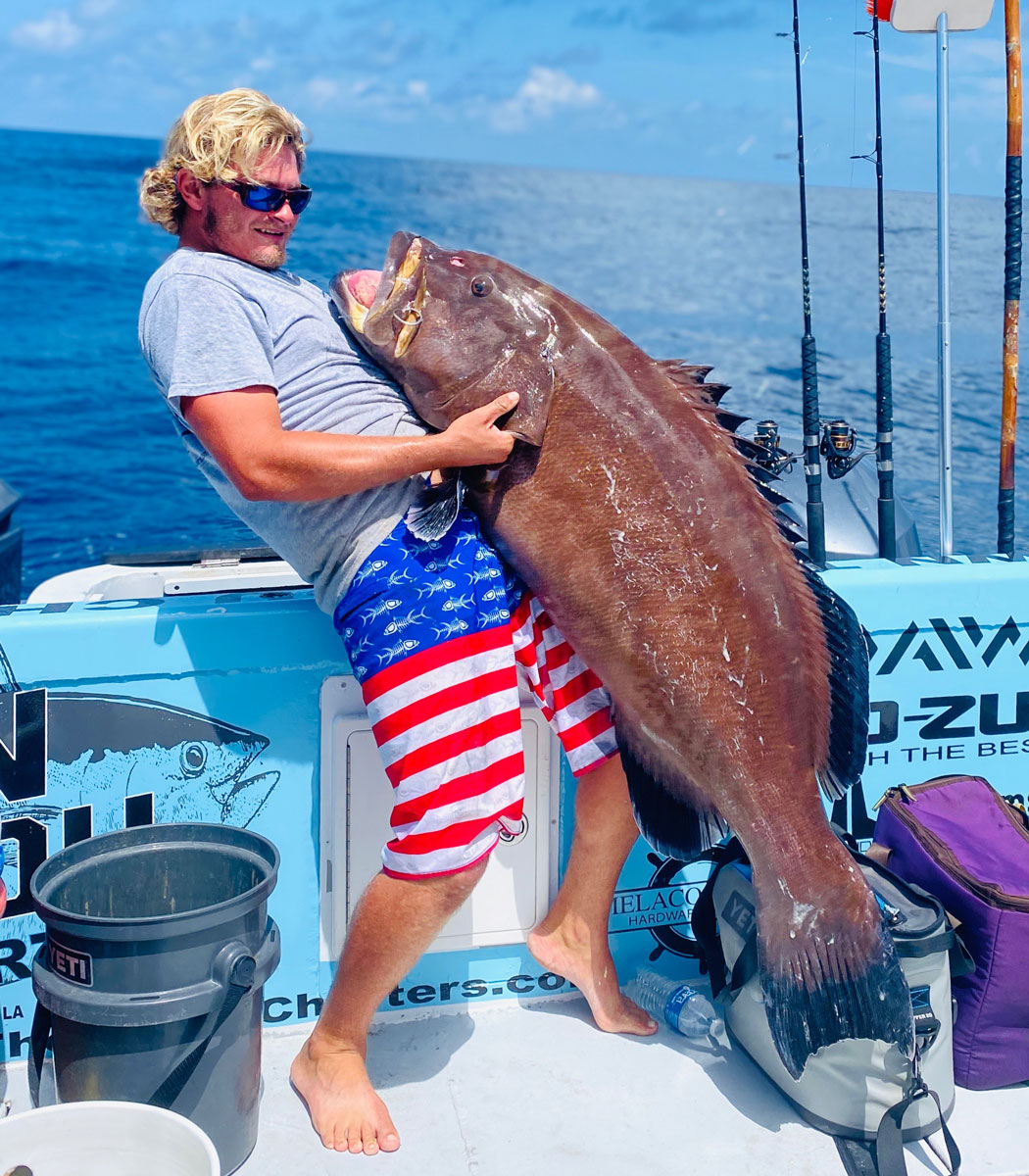 Capt. Ian Buzbee with Down the Bayou Charters lifting the giant grouper.