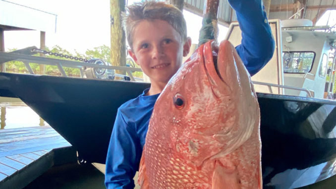 Six-year-old William Bass proudly displays a beautiful red snapper.