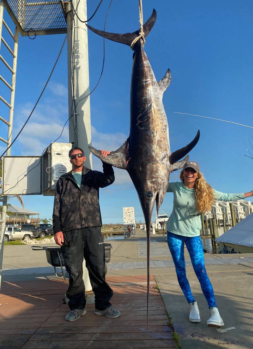 London Rosiere and Capt. Justin Fayard pose with the massive 274.8-pound swordfish she caught recently out of Venice.