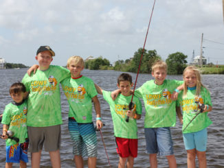 Participants from a Family Fish Fest take a quick break from fishing to pose for a picture. (Photo courtesy LDWF)