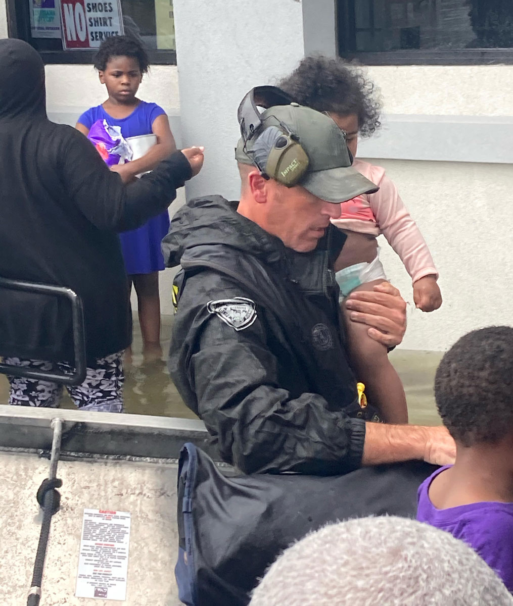 Lt. Beau Robertson carries a little kid above the flood waters to higher ground in Lake Charles. (Photo courtesy LDWF)