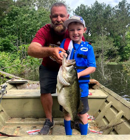 CJ Colvin and his dad Michael pose with CJ's trophy bass.