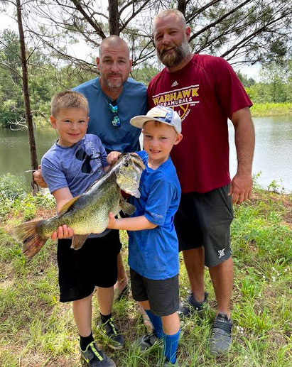 This is why it's important to get kids in the outdoors. Fishing partners Bubby (left) and Michael (right) and their sons Tate (left) and CJ (right) with a trophy and memories for a lifetime.