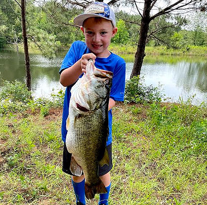 Seven-year-old CJ Colvin and his 13-pound summer largemouth.
