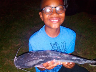 A young angler shows off a tagged catfish during the 2021 Tagged Catfish Derby.