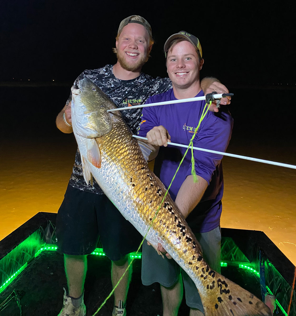 Capt. Jeremy Cable (right) and his younger brother, Jesse Cable, of Lite 'em Up Bowfishing hold a big bull red.