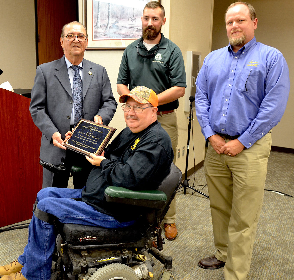 Thad Bellow (center) accepts the Todd Roberts Achievement Award from LDWF Secretary Jack Montoucet (left), LDWF Biologist Educator Supervisor Brad Jackson (center standing) and Hunter Education Program Manager Eric Shanks (right).