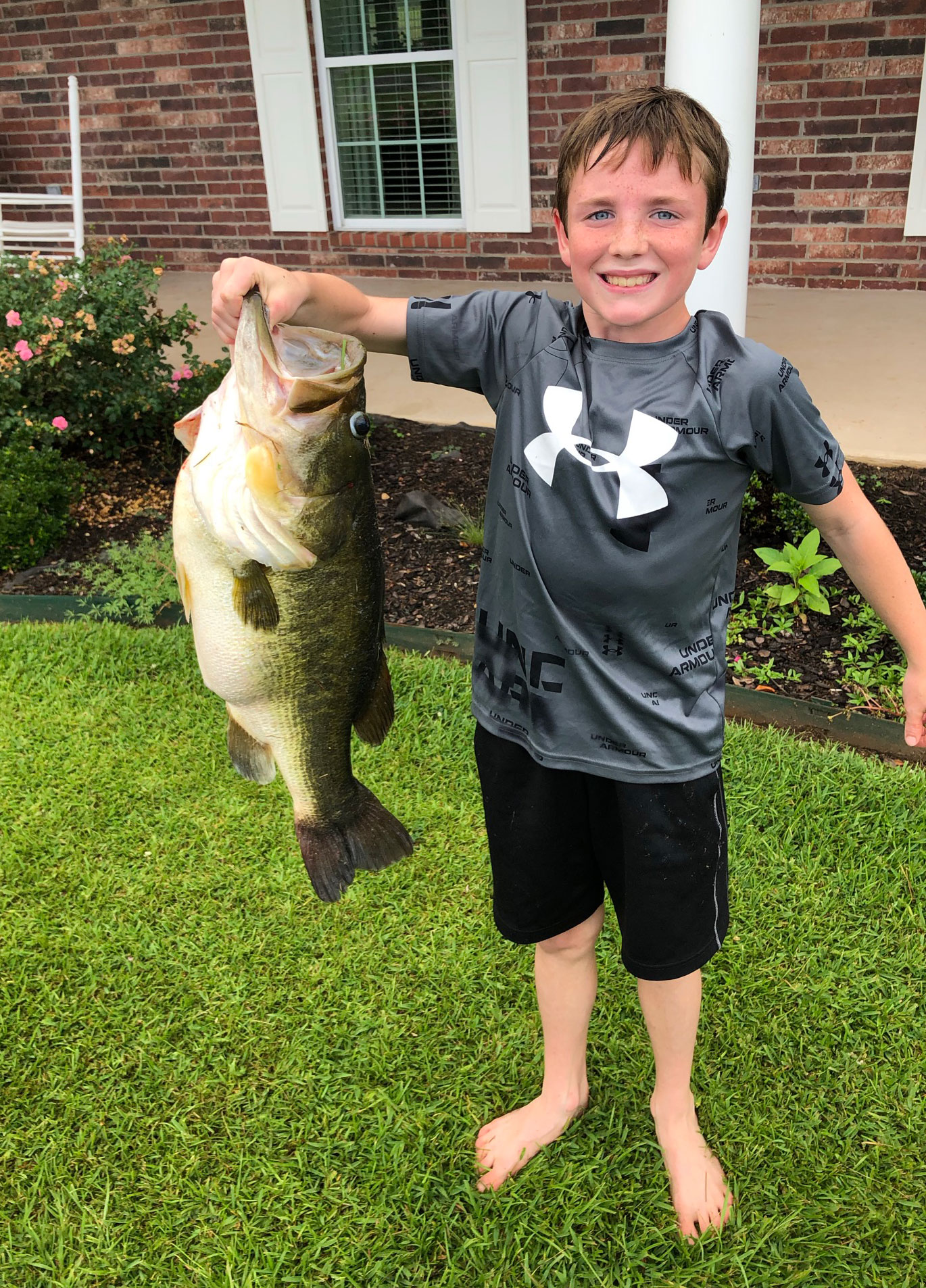 Ten-year-old Landon Smith with the 12.05-pound largemouth bass he caught from a private pond near Atlanta, La., on July 18, 2021.